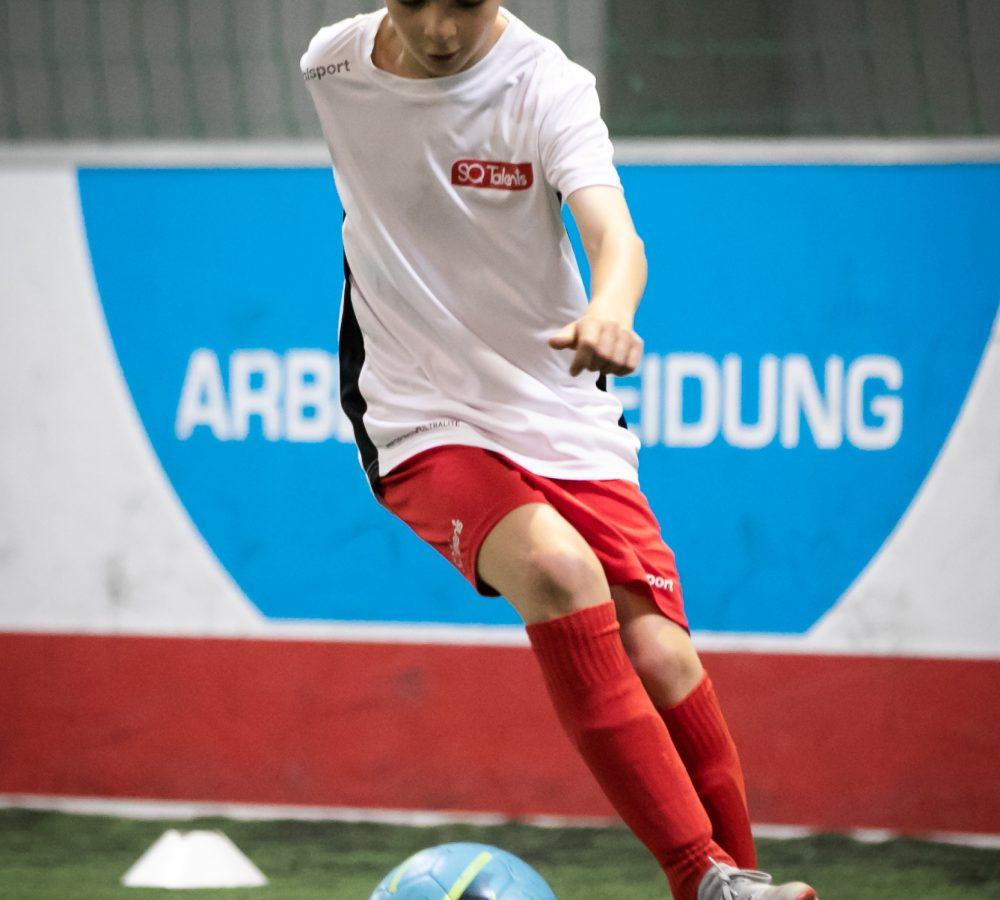 Probetraining Fußball: Junge dribbelt um Hütchen